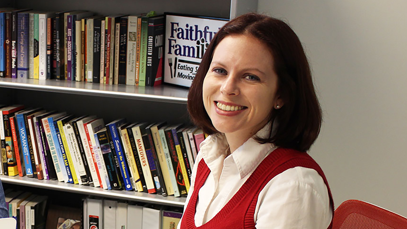 Woman smiling in front of bookshelf